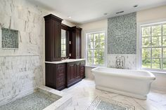 Large bathroom with pedestal tub, blue tiled accents, and large dark wood sink area prominently featured.