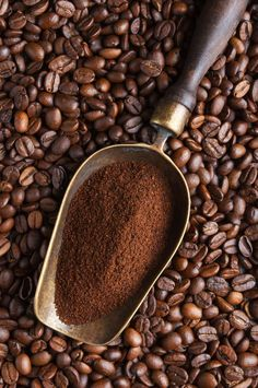 O vintage scoop with ground coffee on coffee beans
