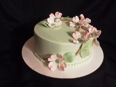 8 inch Chocolate Mud Cake with White Chocolate Ganache Filling and then Iced in Chocolate Ganache and Covered With Fondant. Decorated with a Fondant Border and Branches and Gumpaste Dogwood flowers and Leaves.