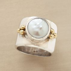 """COIN OF THE REALM RING--A sterling silver band and 18kt gold granulation beads emphasize a freshwater cultured coin pearl. Handmade exclusive. Pearl size may vary. Whole sizes 5 to 9. Tapers from 1/2"""" to 1/4""""W."""