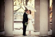 A 1950s Inspired Bride and groom kissing under a parasol