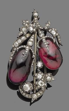 A garnet and diamond brooch, circa 1850. The oval cabochon garnet berries in closed-back settings, the leaves and stems set with rose, old brilliant and cushion-shaped diamonds, mounted in silver and gold.