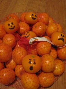 oranges with faces drawn on to look like pumpkins ..great idea for Halloween parties.  I can see these looking great in a clear glass container!