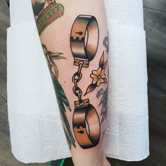 Traditional style golden shackles tattoo by @rabtattoo