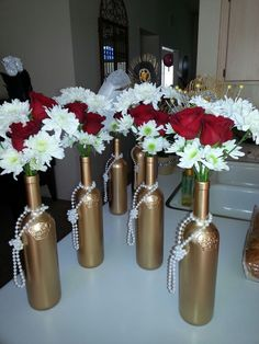 Centerpieces for my Great Gatsby birthday celebration. Used Stella Rosa wine bottles. Removed labels and spray painted them gold.