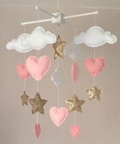 Clouds and stars baby crib mobile. An ideal gift for a new babys nursery or room decor in an older childs bedroom. This mobile consists of five white clouds, five gold stars and seven hearts (two pale shades of pink) in three sizes. The elements are suspended with white thread from either a natural wood or a white wooden mobile hanger. Each element is created with felt or fabric and entirely hand sewn. The clouds and stars are lightly stuffed with hypo-allergenic polyester stuffing. There…