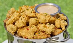A metal pot full of fried alligator nuggets and a small container of honey mustard sauce