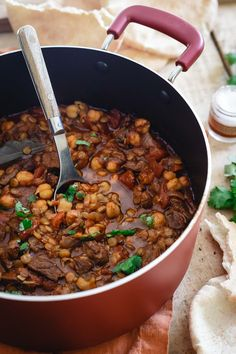This lamb lentil stew is flavored with Moroccan spices and beefed up with chickpeas. Serve with fresh cilantro and a dollop of yogurt for a hearty and comforting winter meal. | #JustAddPulses #HalfCupHabit #sponsored