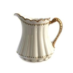 Antique Theodore Haviland Limoges China Pitcher Large 40 oz. White and Heavy Gold  This old and quite rare pitcher is elegant and graceful. There are no chips, cracks, repairs, or crazing. There is minor loss of the hair-line gold at the bottom of the ribbed section. See photo. Otherwise, all other gold is in remarkably wonderful condition.  Measures 6.75 tall x 6.25 at widest part (without handle)  Backstamp dates to 1903. Notice the underlined Theodore Patent Applied for After much…