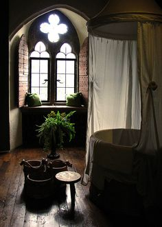 Beautiful boho bathroom in what looks to be a converted church. Stunning window and natural, organic feel.