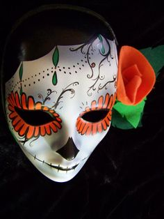 "~~~~~~~~This is a Hand-painted mask from my Daughter Danielle's collection, and features a ""Dia De Los Muertos"" skull theme (Day of the Dead), painted on a very sturdy , primed plastic mask, designed with delicate, brightly colored flowers & delicate black detailing, in orange, bright & dark greens, has a hand formed felt flower to frame her face.   The Mask has a felt back, and is to be placed on the wall or set on a table for display use Only.   It is sure to brighten up any room, makes a…"