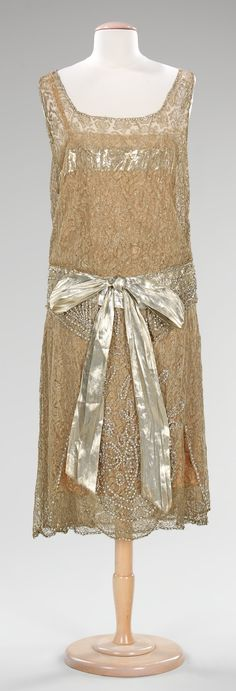 "Evening Dress, Martha Weathered, Inc.: ca. 1925, American, silk, metal, rhinestones. ""The varied light-reflective qualities of silver lace, silver lamé and rhinestones give this evening dress a festive and glamourous quality. Martha Weathered was a high-end women's retailer on Chicago's Michigan Avenue; this piece is an example of a good American-made 1920s dress."""