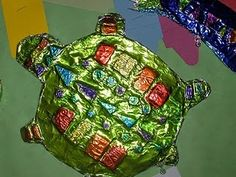 Foil Turtle. Metal Tooling From Dynamic Art Projects for Children- chose an animal and make a sketch of the animal - enlarge onto 12x18 paper - cut the animal out of the paper - cut up styrofoam plates and glued the pieces down to form patterns and designs on the animal. use old cardboard and glued the paper animal with styrofoam pieces to the cardboard -cut the animals out of the cardboard - cover the animals in aluminum foil and then colored with Sharpie markers.