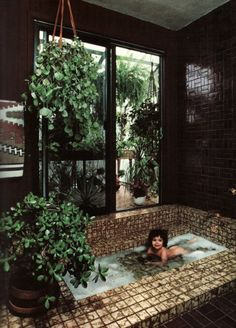 """houseplants in the bathroom add a Bohemian feel"" . I also like this x-large tiled bathtub!"