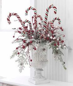 Candy canes in white urn .