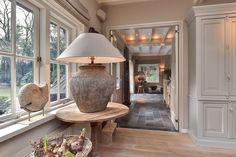 Afwerking, landelijk, sfeervol, lichte kleuren, hout, grijs, wit. Witte speakers. Landelijke kast. Balken plafond.