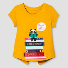 """For the perfect top for your little bookworm, pick up this Cap-Sleeve T-Shirt from Cat & Jack™. With a yellow-orange background, this graphic tee shows a stack of books with a panda holding its own book and a speech bubble that says """"Read to Me!"""" Pair it with leggings or jogger pants for the most comfortable and cute reading outfit around."""