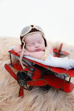 Newborn on airplane with aviator hat