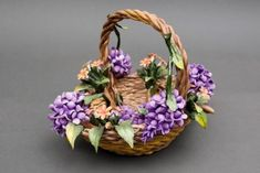 Gracious basket Centerpiece of Purple Wisteria in Capodimonte porcelain finely worked. Each flower is reproduced in detail by the artist and it is then laid on an elegant basket, which is also entirely woven by hand.        Dimensions cm. 20x25