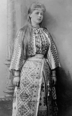 Marie came to Romania as a 17 year old royal bride and immediately adopted the dress of a peasant woman. The chin straps, head blankets and over-sized head gear came later.