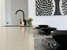 Modern kitchen area with black tap, modern painting, white kitchen bench, black plates Black Plates, Minimalist Design, Modern Painting, White Kitchen Bench, Kitchen Benches, 3 Bedroom House, House, Kitchen, Home Decor