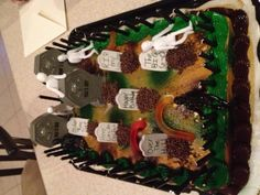 Over The Hill Birthday Cake. I found a plain camo type sheet cake at Walmart. Hopped over to the Halloween section at Walmart and found this edible tombstone cupcake kit for $1.97. Add some stretchie zombies and gummy worms and there you have a cake under $20!