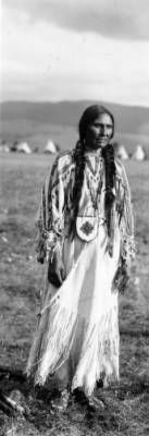 Mrs. John Bushman, a Native American woman on the Flathead Indian Reservation in western Montana, wears a long dress adorned with beadwork and tassles. Strips of fur are wrapped around her long braids, and she has a beaded pouch at her waist. She also wears beaded moccasins. A patterned blanket is piled at her feet. A group of teepees is in the distance at the base of a ridge of mountains.  Date - between 1905 and 1907