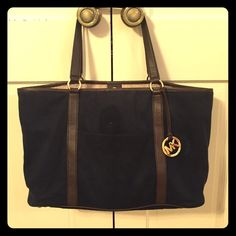 MICHAEL Michael Kors Blue Shoulder Tote Authentic Michael Kors navy blue messenger bag/shoulder tote. Canvas type material, in great condition. Interior tan/taupe colored w snap closure, organizing pocket w zipper, mobile pocket, & 3 other organizing pockets. Dark brown straps, in great condition as well, w gold MK logo & strapping hoops.  Michael Kors Bags Shoulder Bags