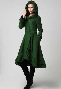 Truly one of a kind, this beautiful wool blend coat has so many gorgeous details, not to mention the striking dark green color. Ultra feminine, the fabulous ruffle detailing can be seen on the hood, sleeve cuffs and two-tiered dipped hem. The coat itself is fully lined in polyester and has elongated sleeves, diagonal hip pockets, a self tie belt, and four fabric-coved button closure **Detail** Wool blend, Full lined with Polyester button fastening through the front, tie belt waist…