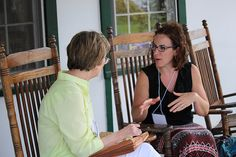 Carol Wedeven and conferee discuss a project on the porch