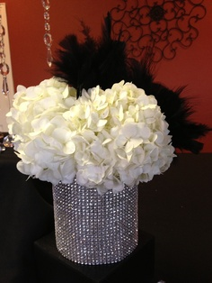 Diamonds and Pearls Themed Party. Black, white and silver color scheme. Flowers are accented with feathers and placed in vases wrapped with rhinestones. Event Planner and Photo by: One Event Design.