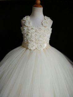 Welcome visiting.  This tutu dress is made of tulle and theres a crystal pearl in the center of each flower. It comes along with a sash on the