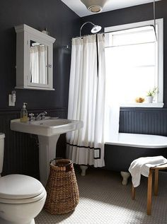 With the versatility of a little black dress, black paint can look sophisticated in every room of your house. Here, gray-black takes a bathroom from quaint to chic, never crossing into stark territory thanks to the addition of natural wood accents.