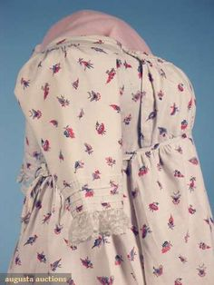 """Augusta Auctions Lot 120 in April '09  c1800 english, printed cotton round gown  White ground printed w/ small scattered red, pink, purple & blue leaves & flowers, gathered 4 band drop front bodice w/ shoulder buttons, center back ties, short tucked sleeves trimmed w/ lace, pair blue threads in selvedge, linen bodice & sleeve linings, B 30""""-34"""", W Adjustable, L 51""""-55"""", (period mend under arm) excellent."""