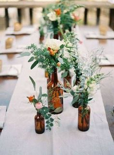 Easy Spring Centerpieces brown bottles with green and white flowers