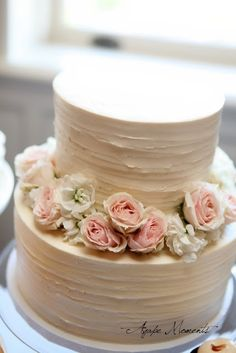 Simply gorgeous two-tier wedding cake with rustic flowers.     Coral  mint/teal  I would like.  More rustic like flowers though.