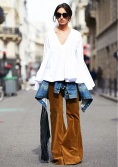 A white ruffled blouse is worn with corduroy flares, a denim jacket, and fringe clutch