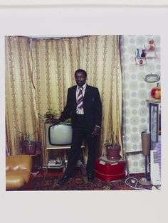 1972 Untitled [A well fully clad man photographed standing by his television in Stockwell, South London,] | Neil Kenlock | V&A Search the Collections