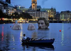 "A man in a rowing boat floats near a ""mermaid"" sculpture created by Oliver Voss on Alster lake in Hamburg. The four-metre-high sculpture dubbed ""Riesen-Nixe"" (grand mermaid or ""Badenixe"" (bathing beauty will be on display until August Oh The Places You'll Go, Places To Visit, All Over The World, Around The Worlds, Mermaid Sculpture, Water Sculpture, Sculpture Art, Public Art, Public Spaces"