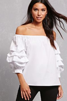 A woven top featuring an elasticized off-the-shoulder neckline and tiered ruffle 3/4 sleeves.