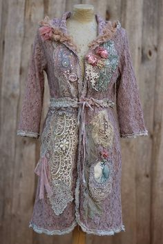 Romantic lacy jacket, reworked with lots of intricate details, hand dyed in shades of soft ecru, mauve,sand and palest purple; adorned with vintage and antique laces and trims at hems- silk and satin rosebuds, vintage oriental trims with sparkling beadwork, vintage ephemera image transfer on canvas, antique handmade lace appliques along vintage and contemporary laces. Material is slightly stretchy cotton/polyester blend. Fastens with ribbons at front. Fits sz M-L measurements: bust 96 cm...