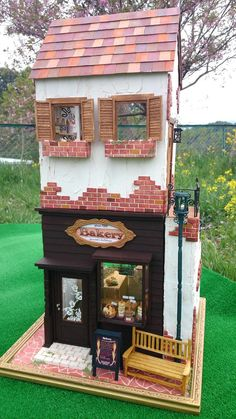 Dollhouse bakery.  I like the way they did the staircase going up on the outside to the 2nd storey. Whimsical, adorable!