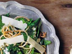 A caper dressing and Parmesan cheese shavings top a kale salad. Deep-fried…