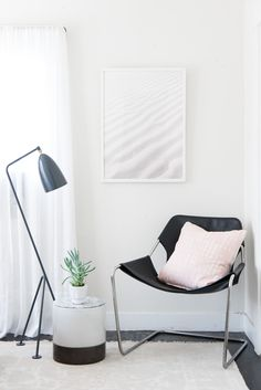 """The """"table"""" next to this Design Within Reach leather sling chair in their bedroom is actually a ceramic planter with a marble platter placed on top of it — """"an instant impromptu storage for odds and ends!"""" The lamp is also from Design Within Reach and the sand dunes photo is from Carley Rudd."""
