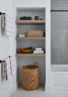 Interior design firm, DGI created this inviting modern farmhouse bathroom for their client's guests. Instead of a traditional linen closet, they opted for open wood shelving with a textural hamper underneath. This adds warmth to the space while also providing easy access for clients to grab towels and other toiletries. Bathroom Linen Closet, Open Bathroom, Upstairs Bathrooms, Bathroom Renos, Basement Bathroom, Bathroom Ideas, Budget Bathroom, Bathroom Towel Shelves, Linen Closets