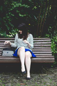 Look com mix de estampas saia azul blusa listrada sapatilha preta e bolsa com estampa quadriculada preto e branco