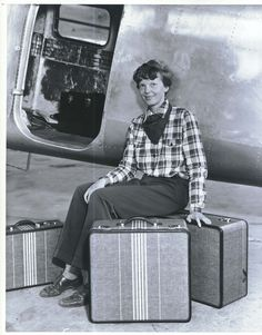 Circa 1935 - Amelia Earhart posing with her own designed luggage, which was sold until the 1990s.