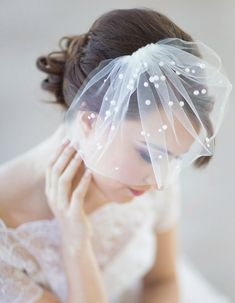 Yes! Tulle birdcage veil with pearls randomly attached to it. I'd want a big (in this case pearl) hair pin or clip to put at the base of my head where the little veil attaches!