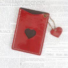 イタリア製の、発色のきれいな皺加工した赤いエナメル革と、最高級クラスの柔らかいシボ感のある黒い牛革をコンビにしたパスケースです。ハート形の穴の開いたカードポケ...|ハンドメイド、手作り、手仕事品の通販・販売・購入ならCreema。