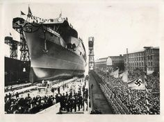 1938-  A huge crowd of spectators gives Nazi salute during the launching ceremonies for Germany's first aircraft carrier, the GRAF ZEPPELIN. Adolf Hitler attended the ceremony.